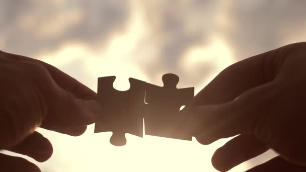 koncepce podnikových financí. mužská ruka spojit životní styl dvě hádanky s siluetou proti západu slunce. symbol týmové práce přidružení a připojení. strategie podnikání