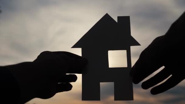 šťastný koncept výstavby rodinných domů. Muž, který drží doma papírový domek ve svých rukou při životním stylu slunce, silueta slunečního svitu. životní ekologie symbol videa