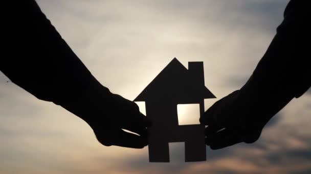 glückliche Familie Bau Haus Konzept. Mann mit einem Papierhäuschen in der Hand im Sonnenuntergang. Life Lifestyle Symbol Ökologie Video