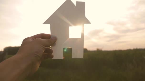 glückliche Familie Bau Haus Konzept. Mann mit einem Papierhäuschen in der Hand im Sonnenuntergang. Leben Symbol Ökologie Video