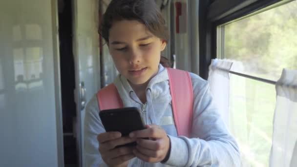 dívčí Mladý cestovatel s batohu u okna vlakového vozu s smartphone. cesta doprava koncept životní styl. dívka ve vlaku u okna odpovídá