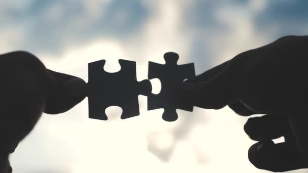 obchodní spolupráce koncepce podnikání koncept životní styl. mužské ruce spojují dvě hádanky s siluetou proti západu slunce. symbol týmové práce přidružení a připojení. obchodní strategie