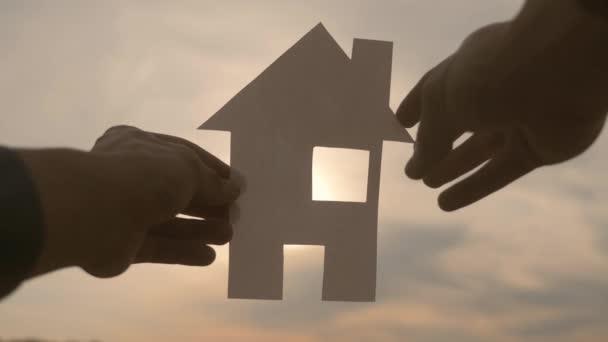 šťastný koncept výstavby rodinných domů. Muž, který drží doma papírový domek ve svých rukou při slunečním svitu siluetě. životní styl ekologie životní video symbol