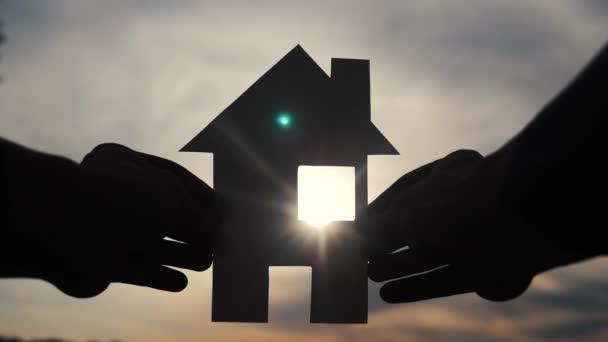 životní styl šťastný Stavba rodinného domu. Muž, který drží doma papírový domek ve svých rukou při slunečním svitu siluetě. ekologie životní video symbol