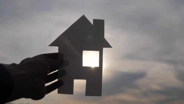 šťastná představa rodinného života v rodinném domě. Muž, který drží doma papírový domek ve svých rukou při slunečním svitu siluetě. životní ekologie symbol videa