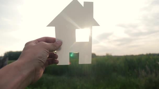 boldog családi építőház koncepció. ember gazdaság otthoni életmód a papírház a kezében naplemente sziluett napfény. élet szimbóluma ökológia videó