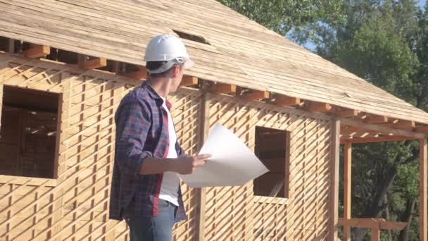 koncept stavba stavba architekt pomalý pohyb videa. stavitel v přilbě, který má v plánu plán domu. Lokalita nedaleko životního stylu dřevěné rámy ve výstavbě