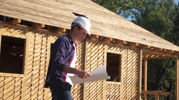 concetto di costruzione architetto video al rallentatore. costruttore uomo in un casco sta in costruzione in possesso di un piano casa schema. vicino a una casa cornice in legno in costruzione. lavoratori lavorano