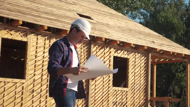 concept building constructing architect slow motion video. man builder in a helmet stands at construction holding a scheme house plan lifestyle . site near a wooden frame house under construction