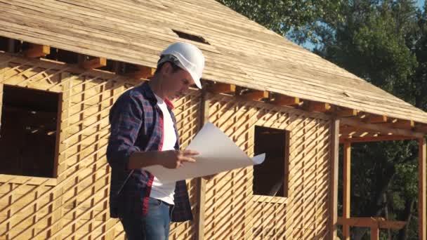 Konzept Gebäude Bau Architekt Zeitlupe Video. Bauarbeiter mit Helm steht auf einer Baustelle und hält einen Plan für ein Haus in der Hand. Grundstück in der Nähe eines im Bau befindlichen Fachwerkhauses