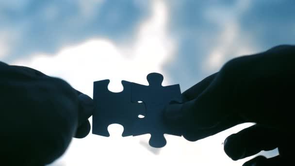 koncepce životního stylu týmovo podnikání finance. mužské ruce spojují dvě hádanky s siluetou proti západu slunce. symbol týmové práce přidružení a připojení. obchodní strategie