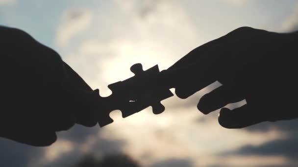 koncepce podnikových financí. mužské ruce spojují dvě hádanky s siluetou proti západu slunce. symbol spolupráce mezi přidružením a připojením. životní styl obchodní strategie