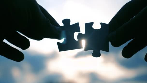 koncepce podnikových financí. mužské ruce spojují dvě hádanky s siluetou proti západu slunce. symbol týmovo asociace a propojení životního stylu. strategie podnikání