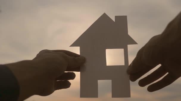šťastný koncept výstavby rodinných domů. Muž, který drží doma papírový domek ve svém životním stylu za slunečních paprsků slunce. životní ekologie symbol videa