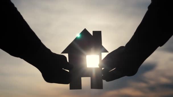 šťastný rodinný stavební život. Muž, který drží doma papírový domek ve svých rukou při slunečním svitu siluetě. životní ekologie symbol videa