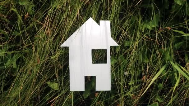 boldog családi építőház koncepció. papír ház áll a zöld fű az életmód természete. élet szimbóluma ökológia videó