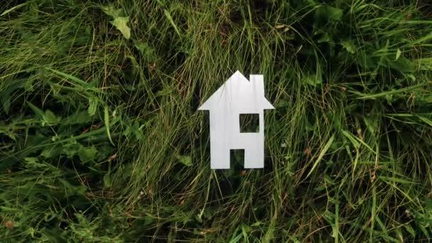 glückliche Familie Bau Haus Konzept. Lifestylehaus aus Papier steht im grünen Gras in der Natur. Leben Symbol Ökologie Video