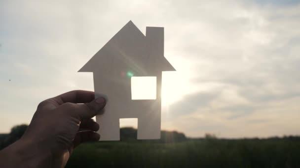 šťastný koncept rodinného stavebního domu. muž životního stylu, který drží doma papírový domek ve svých rukou při slunečním svitu siluetě. životní symbol ekologie video