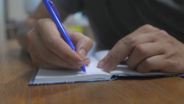 man writes in notebook. male hand writing in a notepad. concept business education. man makes notes in notebook that lifestyle lies on the table