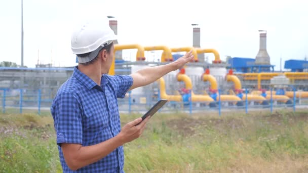 teamwork gas production station concept. Engineering man standing writes documents on digital tablet white safety helmet. man engineer in helmet work at the station are studying on lifestyle gas