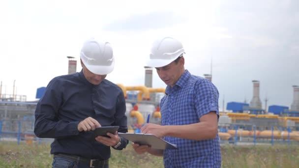 Teamwork. Industrie-Tankstellenkonzept. Zeitlupenvideo. Zwei Ingenieure in Helmen studieren die Arbeit mit einem digitalen Tablet in einem Factorygas Lifestyle-Liefervertrag. zwei