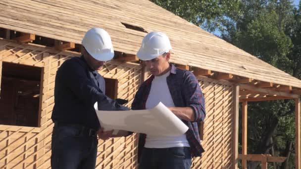 Týmová práce. koncept stavba stavba architekt pomalý pohyb videa. dva muži stavitel v helmicích studují plán domu. dva architekti pracující v životním stylu na stavbě stavebního domu