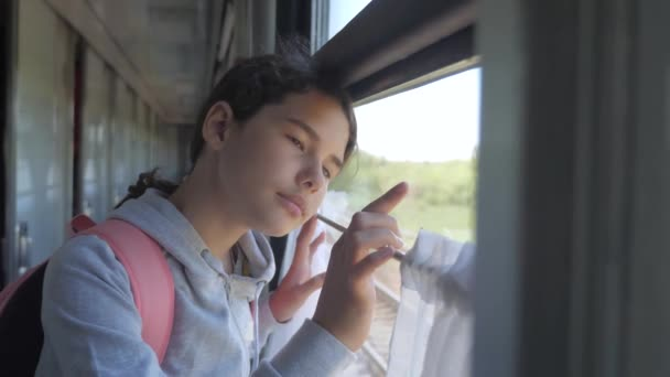 sad girl looks out the train window. travel transportation railroad concept. teen girl misses traveling in a train compartment looking out the window lifestyle . long train journey by rail