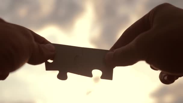 teamwork business finance concept. male hands connect two puzzles silhouette against the sunset. lifestyle teamwork symbol of association and connection. strategy business