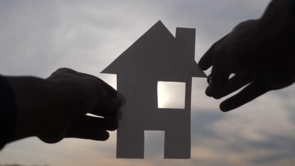 šťastný koncept výstavby rodinných domů. Muž, který drží doma papírový domek ve svých rukou při pozorování slunečních paprsků. ekologie životní video symbol