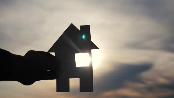 šťastný koncept rodinného stavebního domu. Muž, který drží doma v rukou životní styl papíru při západu slunce. životní ekologie symbol videa