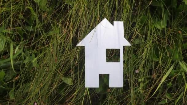 životní styl šťastný rodinný stavební dům. v zelené trávě v přírodě stánky s papírovým domem. životní symbol ekologie video