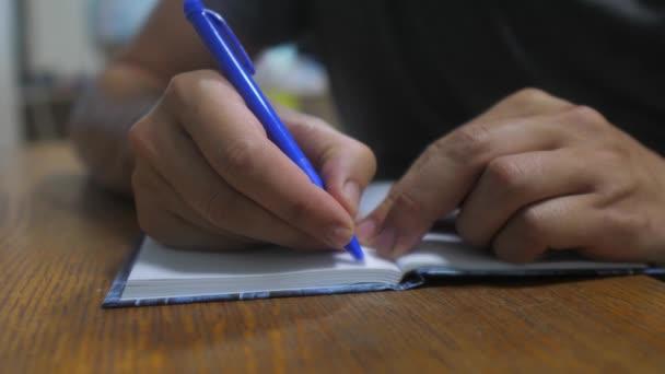 ember életmód leír-ban jegyzetfüzet. Mans kézzel írt egy jegyzettömböt. koncepció üzleti oktatás. ember ideiglenes tákolmány jegyzék-ban jegyzetfüzet amit fekszik-on asztal