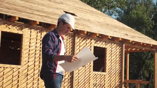 koncepcióépület építése építész lassított videó. ember építője egy sisakot áll építőipari gazdaság rendszer ház tervet. telek közelében egy fából készült váz ház alatt. dolgozónak dolgozik