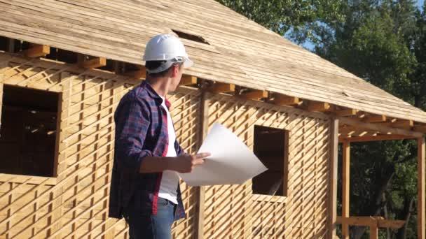 Konzept Gebäude Bau Architekt Zeitlupe Video. Bauarbeiter mit Helm steht am Bau und hält einen Plan für ein Haus in der Hand. Standort in der Nähe eines im Bau befindlichen Fachwerkhauses