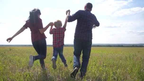 šťastná rodina provozuje přírodu teampráce přátelství péče koncept pomalý pohyb video. otec mamka a syn v přírodě na slunci slunce drží dlaň na životní styl. šťastné rodinné rodiče muž a dívka drží malého chlapce