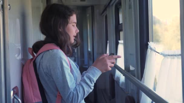 little girl walks on a train compartment car with a backpack and a smartphone. travel transportation railroad concept. the girl in the train at the window corresponds the girl in the train wagon at