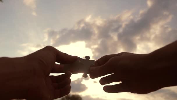 koncepce podnikových financí. mužské ruce spojují dvě hádanky s siluetou proti západu slunce. symbol týmové práce s životním stylem a připojením. obchodní strategie