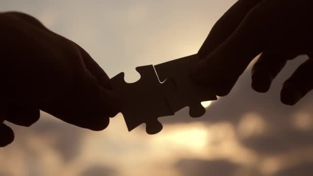 teamwork lifestyle business finance concept. male hands connect two puzzles silhouette against the sunset. symbol teamwork of association and connection. strategy business