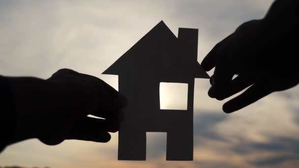 šťastný koncept výstavby rodinných domů. Muž, který drží doma papírový domek ve svých rukou při slunečním svitu ve stylu slunce. ekologie životní video symbol