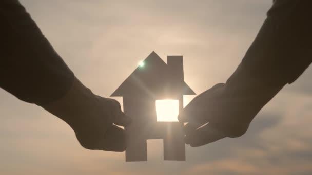 šťastný rodinný život koncepce stavby. Muž, který drží doma papírový domek ve svých rukou při slunečním svitu siluetě. životní ekologie symbol videa