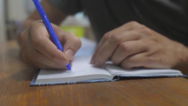 muž píše v poznámkovém bloku. psaní rukou v poznámkovém bloku. koncept životní styl obchodní vzdělávání. muž dělá poznámky v poznámkovém bloku, které leží na stole