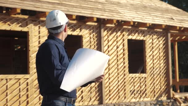 concept building constructing architect slow motion video. man builder in a helmet stands at a construction holding a scheme house plan. site near a wooden frame house under construction. worker works
