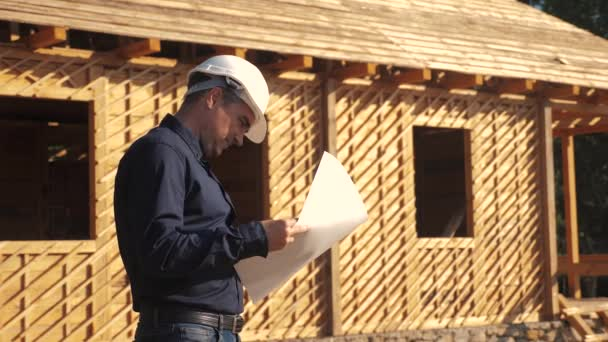 concept building constructing architect slow motion video. man builder in a helmet stands at a construction holding a scheme house plan. site near a lifestyle wooden frame house under construction