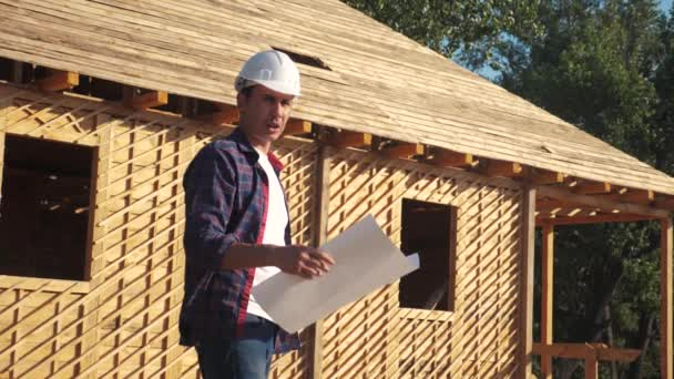 concept building constructing architect slow motion video. man builder in a helmet stands at construction holding a scheme house plan. site near a wooden frame house under construction lifestyle