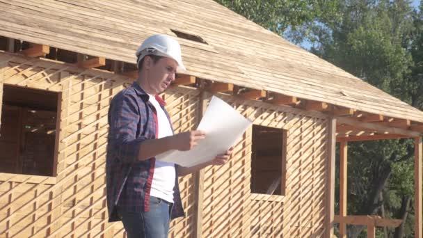 KonzeptGebäude Bau Architekt Zeitlupe Video. Mann Bauherr in einem Helm steht auf dem Bau halten ein Schema Lifestyle-Haus-Plan. Grundstück in der Nähe eines holzigen Rahmenhauses im Bau