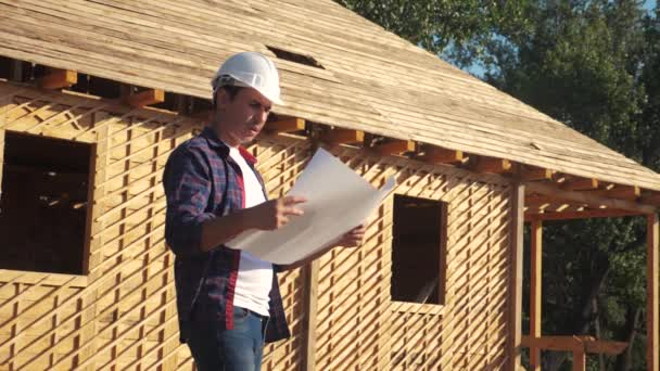 concept building constructing architect slow motion video. man lifestyle builder in a helmet stands at construction holding a scheme house plan. site near a wooden frame house under construction