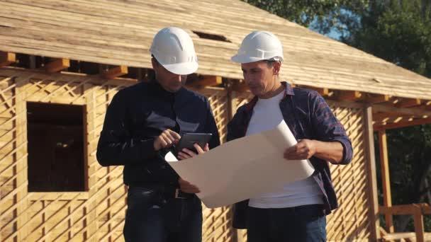 Teamwork. Konzept Gebäude Bau Architekt Zeitlupe Video. Zwei Männer in Helmen studieren den Grundriss des Hauses. Zwei Architekten, die am Bau des Fachwerkhauses arbeiten, kontrastieren bei