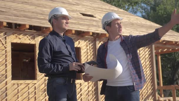 teamwork. concept building constructing architect slow motion video. two men builder in helmets study digital tablet the house plan. two architects working on construction of frame house business