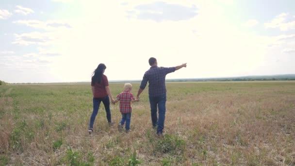 glücklich Familie Teamwork Freundschaft Pflege Konzept Zeitlupe Video. Vater, Mutter und Sohn gehen in der Natur bei Sonnenuntergang Hand in Hand. Lebensstil glückliche Familieneltern Mann und Mädchen halten kleinen Jungen an der Hand