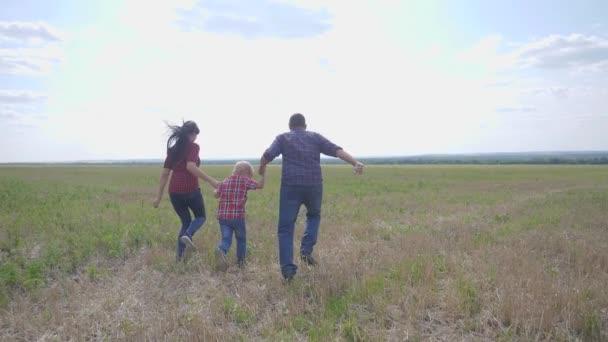glücklich Familienbetrieb Teamwork Konzept Zeitlupe Video. Vater Mutter und Sohn, die in der Natur bei Sonnenuntergang laufen, halten sich an der Hand. glückliche Familieneltern Mann und Mädchen halten kleinen Jungen, der schnell glückliche Hand im Freien läuft